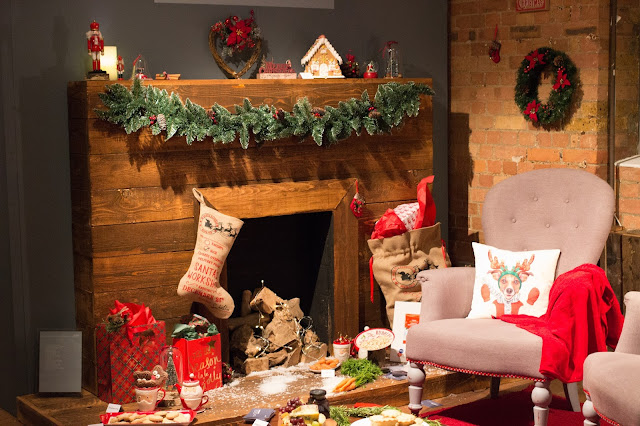 A display fireplace with chairs, stocking and other Christmas decor