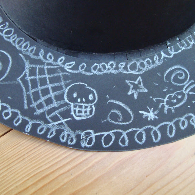 A witches hat brim decorated with halloween doodles.