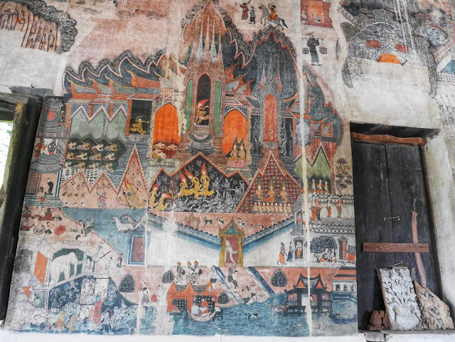 orange, blue, and white temple murals depicting scenes from Lao life and myths