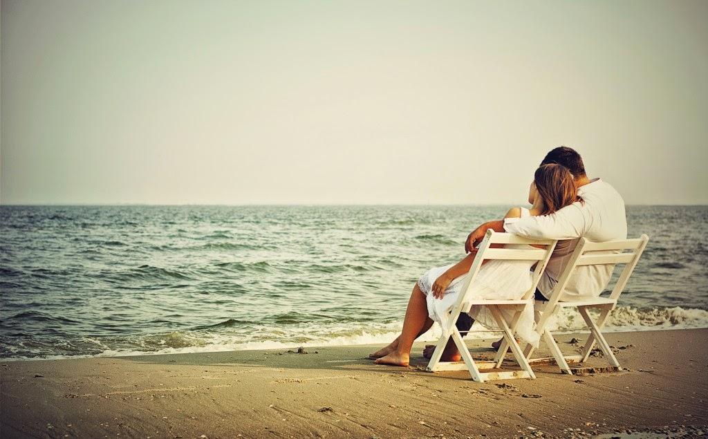 Pareja sentada mirando mar