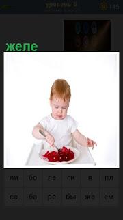 мальчик ложкой ест красное желе на тарелке
