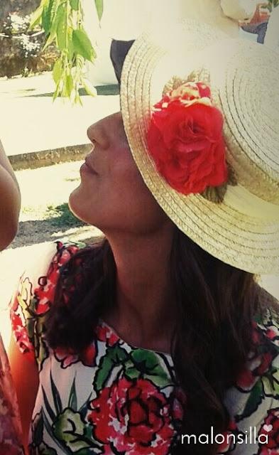 Invitada boda de verano de perfil con vestido estampado largo midi con flores rojas y fondo blanco, sombrero canotier con cinta blanca y flores rojas