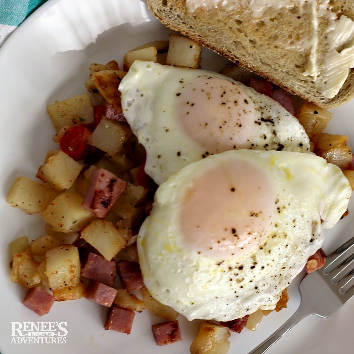 Ham Hash by Renee's Kitchen Adventures on a white plate topped with sunny side up eggs and a piece of toast at the edge of the plate