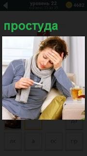 Девушка  за столом с перевязанным горлом шарфом меряет температуру и рядом кружка чая от простуды, схватившись рукой за свой горячий лоб