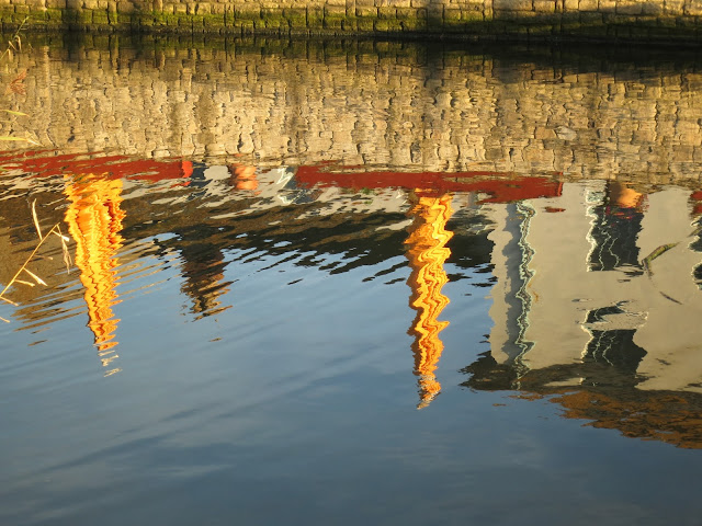 Huge yellow pub umbrellas reflected in the water at West Bay, Dorset
