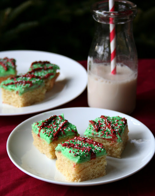 close up of three low carb and gluten free sugar cookie bars with green frosting and nonpareil sprinkles on a white plate and red tablecloth and more milk and cookies in the background