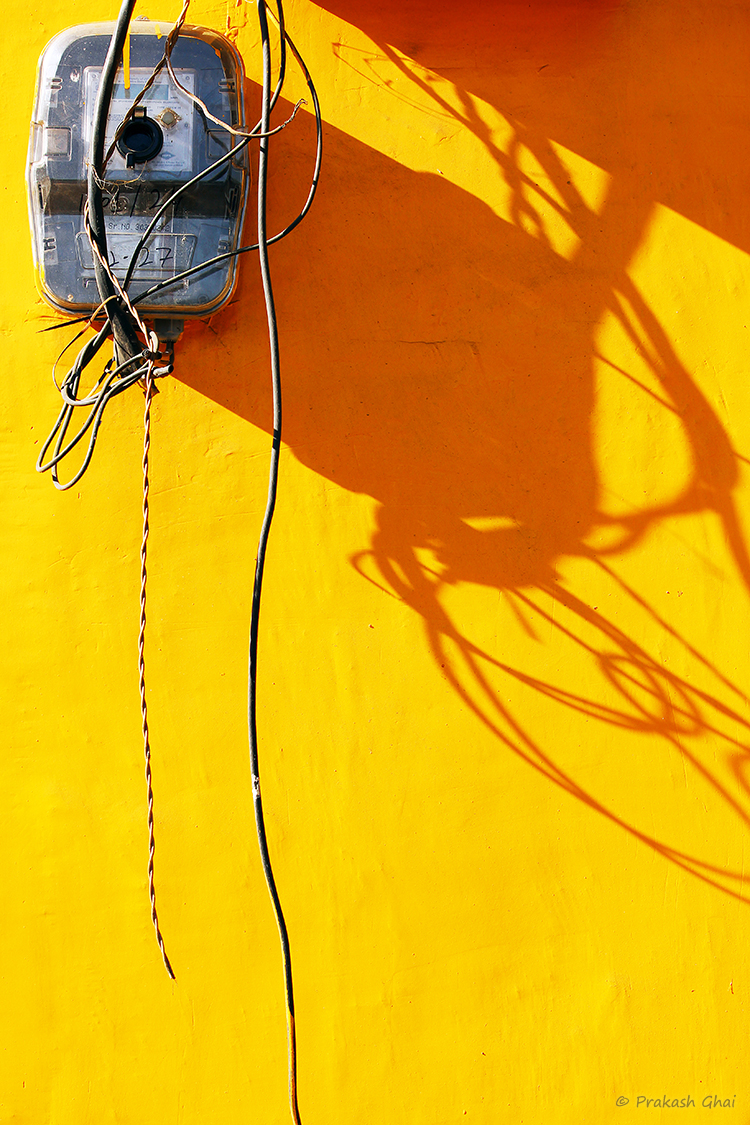A minimalist photo of An Electricity meter against a yellow wall with elongated shadow.