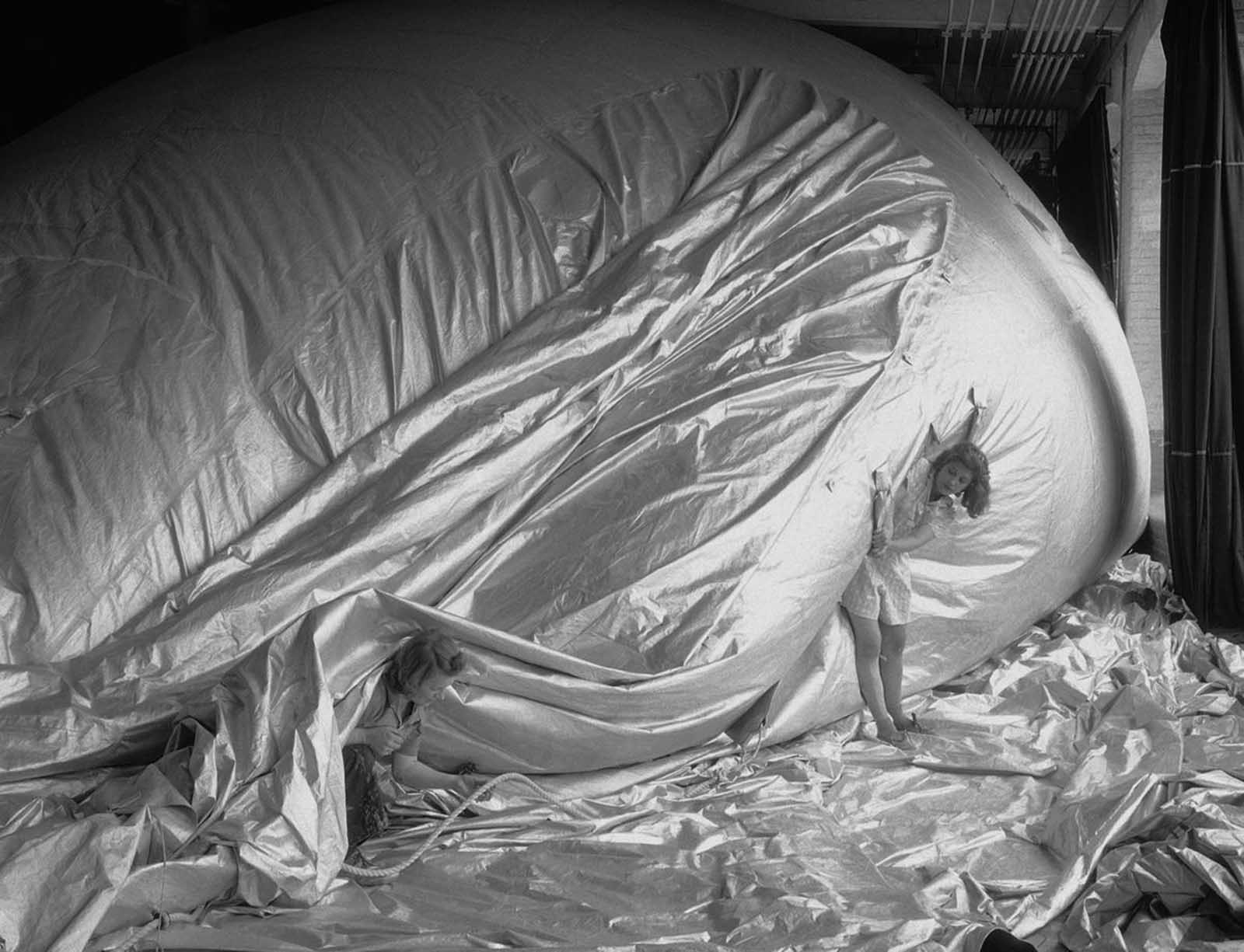 El 11 de mayo de 1943, las trabajadoras inspeccionan un globo de presa parcialmente inflado en New Bedford, Massachusetts. Cada parte del globo debe ser sellada por el trabajador que realiza el trabajo en particular, también por el inspector de trabajo de la división y, finalmente, por el