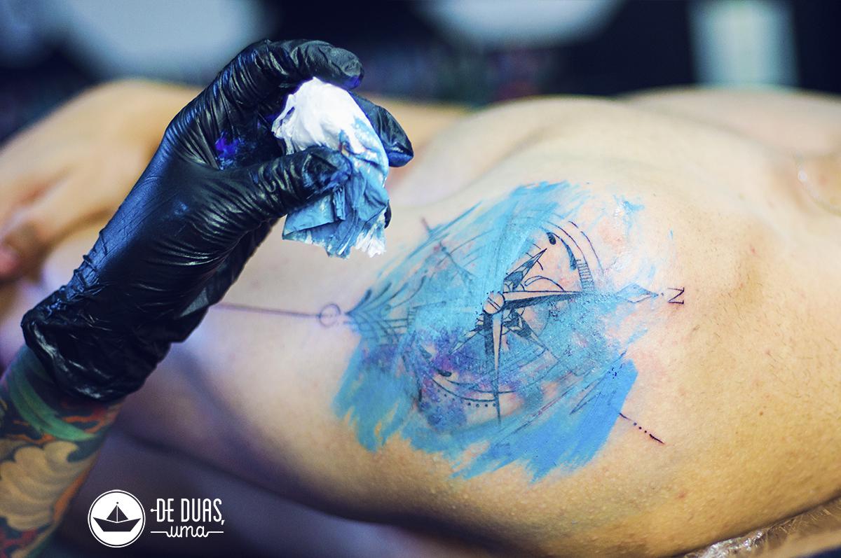 rosa dos ventos aquarela sendo tatuada BH