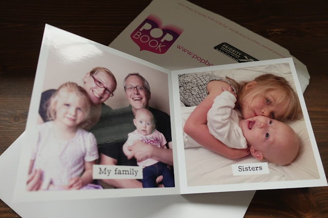 "The first 2 pages of the photo book showing a family portrait called ""my family"" and 2 girls hugging called ""sisters"" book rests on top of envelope with the POP BOOK image showing"