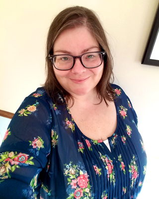 image of me wearing a navy chiffon top with a rose print