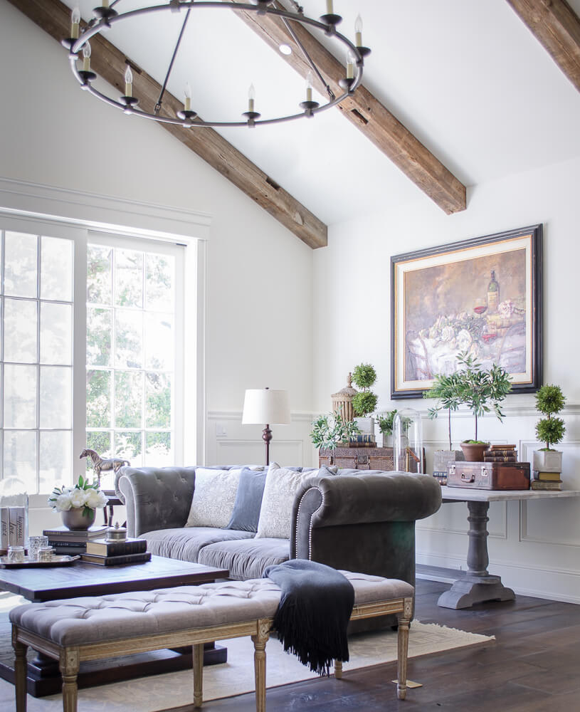 light living room with tufted sofa and wood beams