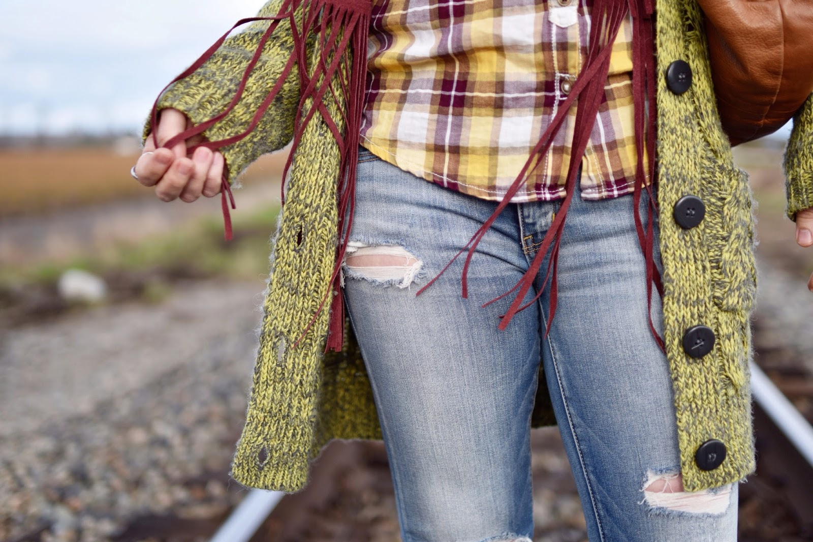 Monika Faulkner outfit inspiration - plaid shirt, fringy suede vest, distressed jeans, slouchy cardigan