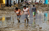 Residents cross a flooded street after rivers breached their banks due to torrential rains in Juarmey, Ancash, Peru on March 22, 2017. (Credit: Reuters/Guadalupe Pardo) Click to Enlarge.