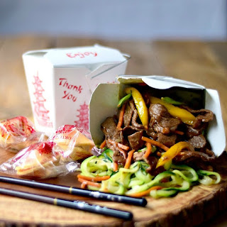 Beef Zoodle Stir Fry spilling out of a take-out container on a wooden board with chopsticks and fortune cookies