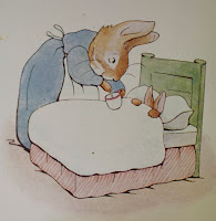 A Beatrix Potter illustration of a rabbit tucked into bed so that only ears and paws are visible, while a larger rabbit in a dress and apron leans over the bed with a cup.