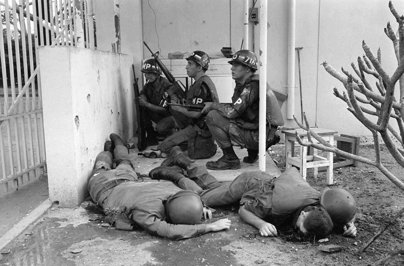 With dead U.S. soldiers in the foreground, U.S. military police take cover behind a wall at the entrance to the U.S. Consulate in Saigon on the first day of the Tet Offensive, January 31, 1968. Viet Cong guerrillas had invaded the grounds of the U.S. embassy compound in the earliest hours of the coordinated Communist offensive.