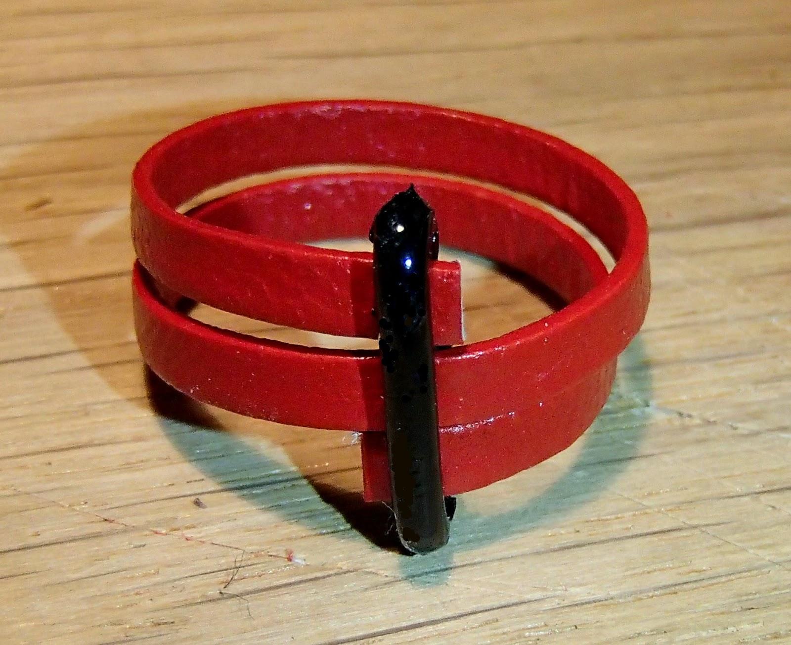 Vue de face d'une bague verticale rouge en cuir plat