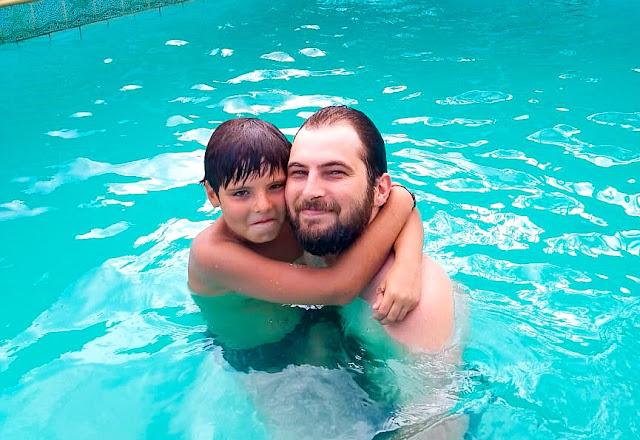 Foto de pai e filho na piscina.