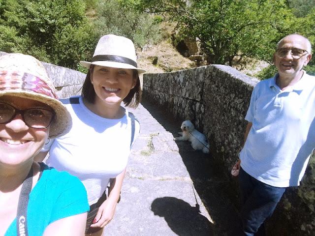 senhor e duas senhoras e um cão numa ponte medieval