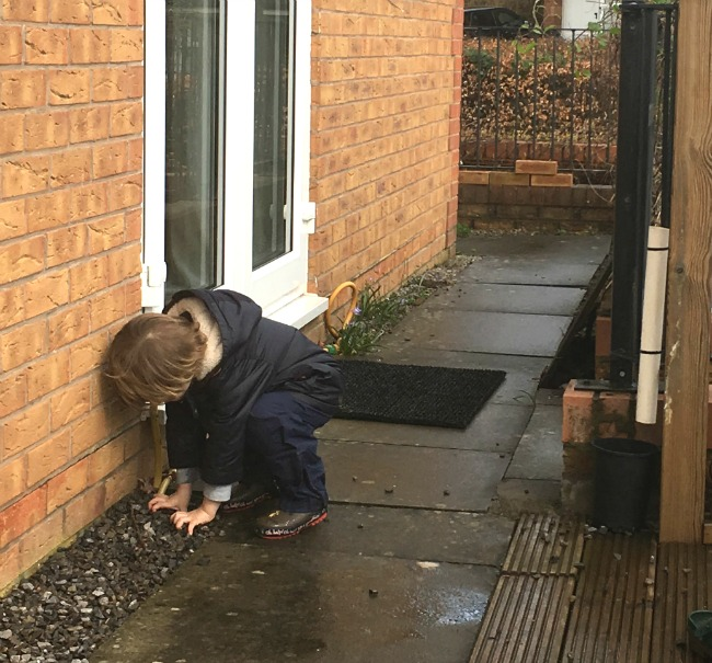 5-minute-games-for-toddlers-down-the-drain-pipe-image-of-toddler-collecting-stones-in-a-garden