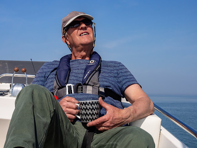 Photo of Phil having a cup of tea on the flybridge while waiting for a bite