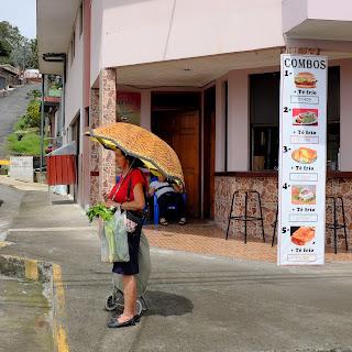 Woman with umbrella on Puriscal street corner.