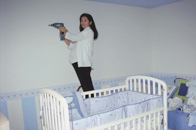 crib with blue bedding, stripes on wall
