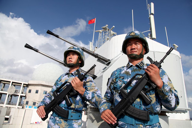 Chinese soldiers of the People's Liberation Army Navy stand guard in the Spratly Islands, known in China as the Nansha Islands, on February 10. The Spratlys are the most contested archipelago in the South China Sea.