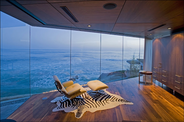 Picture of modern white chair by the glass wall overlooking the ocean