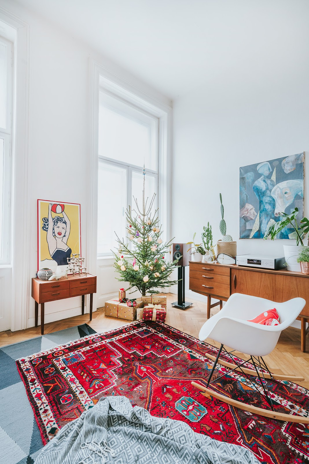 boho interior with a christmas tree, oriental rug and mid century modern furniture.