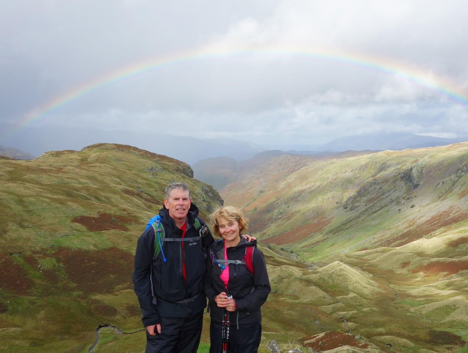 Gail and John Hanlon below a rainbow hiking in the Borrowdale Valley