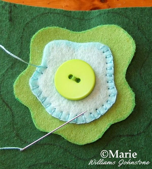 Green cut pieces of material with button and blanket stitching