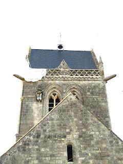 Sainte Mère Eglise Kirchturm mit Soldaten John Steele und Fallschirm
