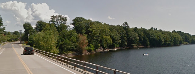under partly cloudy sky, dark blue car crosses bridge over tree-shrouded lake in summer