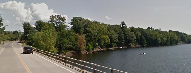 under partly cloudy sky, dark blue car crosses bridge over tree-shrouded lake in summer
