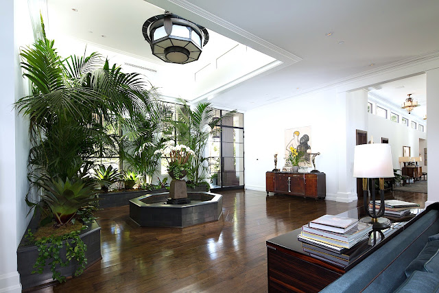 Mansion foyer dark wood floor built in planters sky light