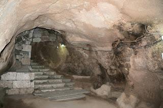 Каппадокия знаменита своими подземными городами, вырубленными в скалах первыми христианами, которые спасались в пустынных уголках Малой Азии в период правления императора Диоклетиана. Много веков в этих пещерах проживали люди. Около полвека назад неподалеку от каппадокийской деревушки Деринкую археологи обнаружили подземные города, уходившие вглубь земли более чем на десятки метров, представленные километровыми лабиринтами галерей, жилых и хозяйственных помещений. На семи ярусах подземелья находятся амбары, колодцы, трапезные, вентиляционные шахты, конюшни, винные погреба, тюрьма, церковь и школа. Дверью, закрывавшей ходы в пещерные города, служили огромные каменные валуны.   Подземный город Деринкую в Каппадокии. Турция. Фото   Сохранить секреты подземелья – было главной целью жителей города, от которой зависела их жизнь. В дни, когда в город наведывались арабы или даже монголы жители уходили под землю. В переходах и штольнях хранились запасы провизии. У всех городов были потайные выходы. Многоярусность, вентиляция и потайные выходы делали такой город безопасным и неприступным.