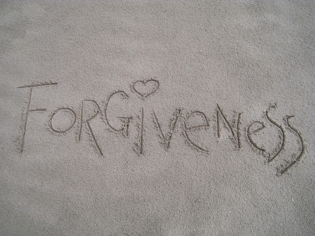 'Forgiveness' written in sand