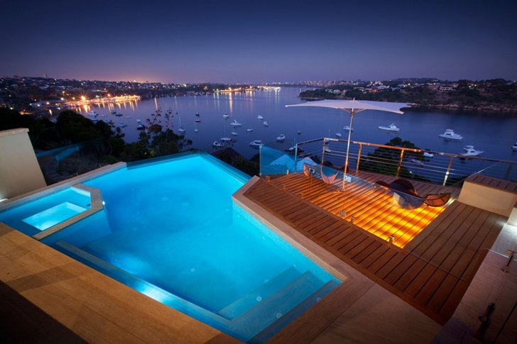 Swimming pool at night in Modern backyard by Ritz Exterior Design