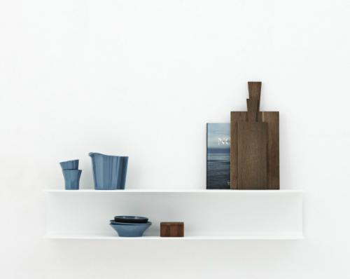 Das weiße Regal in U-Form ist schön mit dunklen Holzbrettern und blauen Schalen und Tassen dekoriert