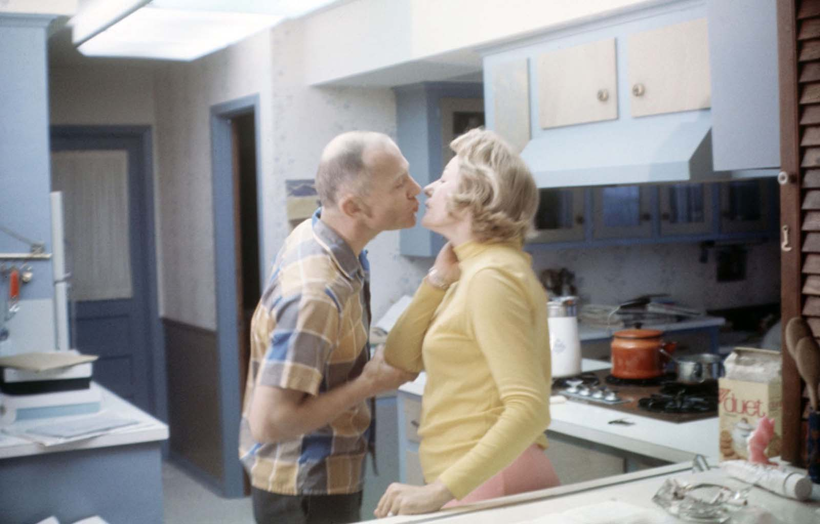 Buzz and Joan Aldrin share a kiss in the kitchen of their Texas home.
