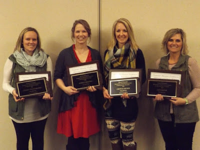 Photo of four teachers holding awards.