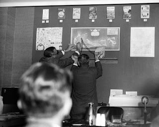 A black and white photograph of two men holding a dowsing rod up against a map on a wall.