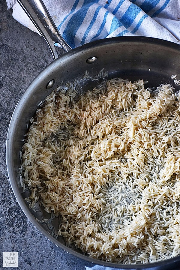 Toasting rice in a skillet for Teriyaki Chicken Rice Bowl
