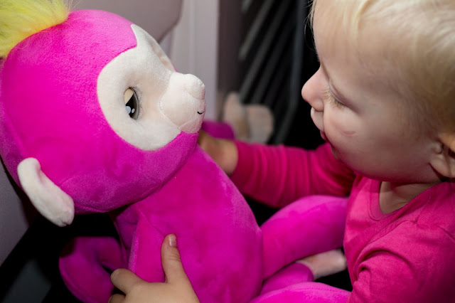 A toddler talking to a pink soft plush monkey