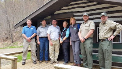 Staff of PHMC and DCNR standing in front of Webber Cabin