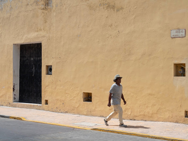 Hombre con sombrero caminando frente a una fachada amarilla en Valladolid, Yucatan
