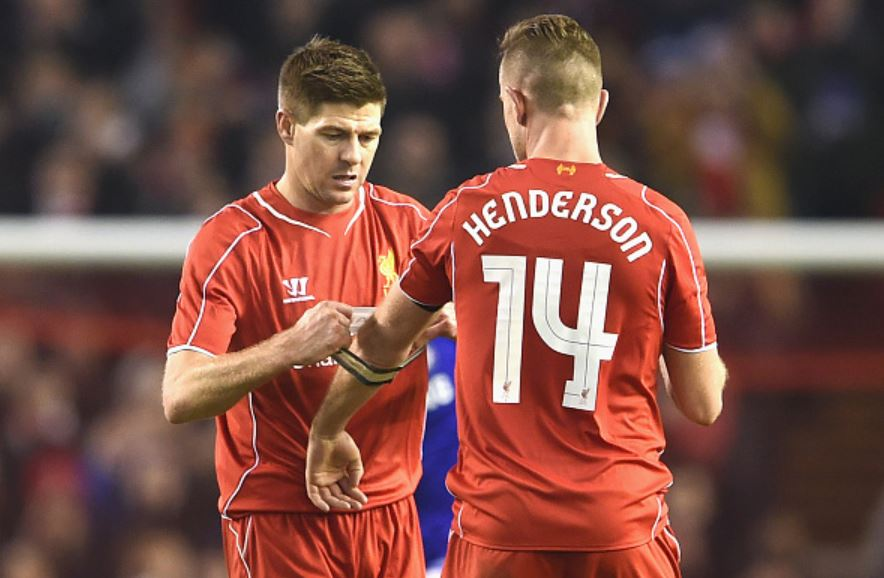 Gerrard-hands-captain-armband-to-Henderson-on-pitch