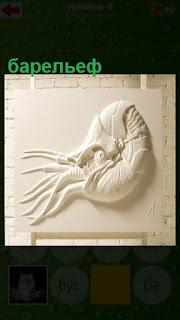 на стене сделан барельеф осьминога белого цвета